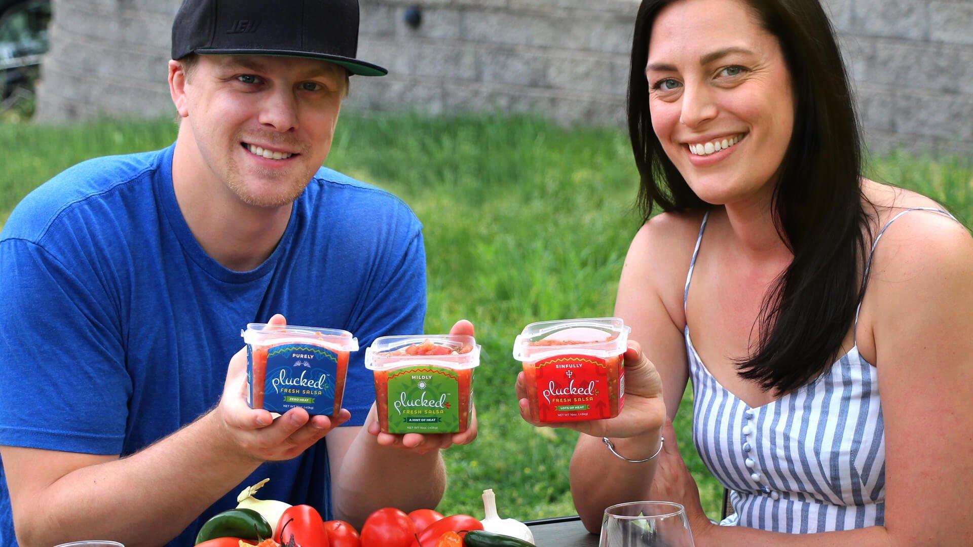 couple holding Plucked Fresh Salsa in backyard